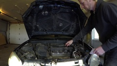 Man checking his oil under the hood Stock Footage