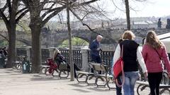 People rest enjoy the view, sit on bench, Vltava river, Prague, Czech Republic Stock Footage