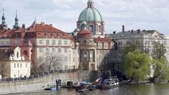 Docked boat, flags, Saint Francis dome church, Prague skyline, Czech Republic Stock Footage