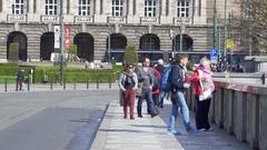 People walk across Mánes Bridge, busy city street, Prague, Czech Republic Stock Footage