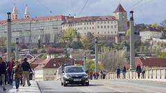Cars people and tram cross Mánes Bridge, Prague cityscape, Czech Republic Stock Footage