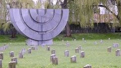 Theresienstadt Jewish cemetery, stone Menorah memorial, side medium shot Stock Footage