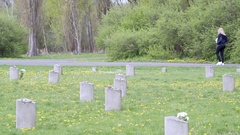 Tourists at Theresienstadt Jewish cemetery, stone memorial, Terezin, Czech R. Stock Footage
