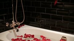 Black bath with water and petals of red roses Stock Footage