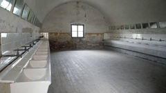 Crumbling bathroom washroom, many sinks, mirrors, Theresienstadt camp Stock Footage