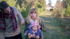 Portrait of a mother, father and their baby girl at a Christmas tree farm Stock Footage