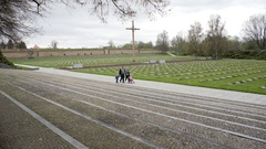 Family walk across Theresienstadt victims memorial graves, Christian cross Stock Footage