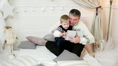 Family reading a book, loving father reads a book to his son, while spending Arkistovideo