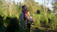 A young mother and father with their baby choosing a Christmas tree Stock Footage