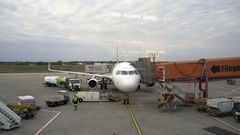 Parked airplane, jet bridge gate, ground crew refueling, Tegel Airport, Berlin Stock Footage