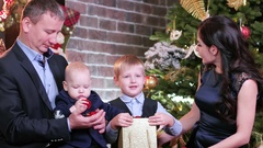 Family celebrating new year, mom dad and sons watching Christmas gifts sitting Stock Footage