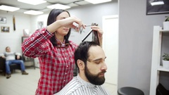 Barber cuts the hair of the client with scissors. Slow motion Stock Footage