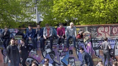 Group of young people sit on graffiti wall, 1st of May, Gorlitzer Park, Berlin Stock Footage