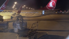 Ground crew prepares to unload luggage from Turkish Airways airplane Stock Footage
