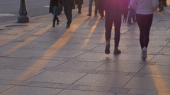 Bottom view of people legs against sunset rays on the paving stone Stock Footage
