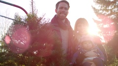 Portrait of a young mother, father and their baby girl at a Christmas tree farm Stock Footage