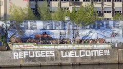 Refugees Welcome graffiti on wall, long shot, Berlin, Germany Stock Footage