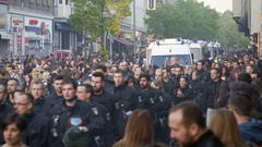 Riot police officers and vans march through crowded Berlin street, Germany Stock Footage