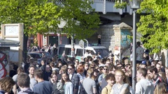 Crowd of people, police cars, 1st of May, labor day, Gorlitzer Park, Berlin Stock Footage