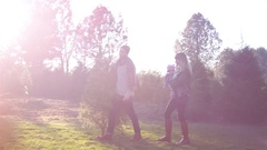 Man carries a Christmas tree through the farm, walking with his wife and baby Stock Footage