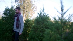 Man carries a Christmas tree through the farm, wife and daughter following Stock Footage