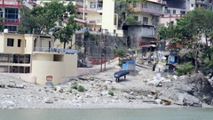 Two people carry water raft up Ganges river bank, Rishikesh, India Stock Footage