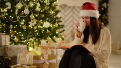 Laughing Woman in Santa Hat Siting Next to Christmas Tree and Holding an Opened Stock Footage
