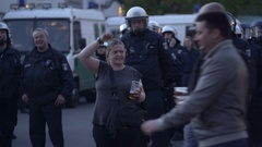 Drunk woman with bear mocking riot police officers, labor day, Berlin Stock Footage