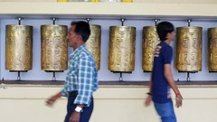 Men walk past each other, Buddhist prayer wheels, Dalai Lama Complex Stock Footage