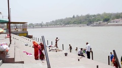 People bathe and shower at holy Ganges river, Ram Jhula Ghat, Rishikesh Stock Footage