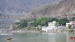 People cross Lakshman Jhula bridge, rafting in Ganges river, Rishikesh, India Stock Footage