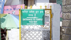 Entrance to Temple This Way sign, Hindi and English language, India Stock Footage