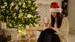Beautiful Young Woman Wearing Santa Hat Sitting at Home and Having Hot Beverage Stock Footage