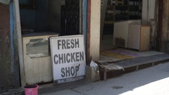 Fresh Chicken Shop sign, people walk in front, Mcleod Ganj, India Stock Footage