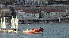 4K Sailor instructor children group sailing school in Athens city coast skyline Stock Footage