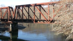 Old railroad bridge pan over moving river Stock Footage