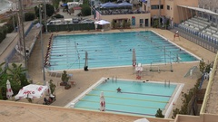 4K People swimming in outdoor pool practice wealthy water sport in Athens town Stock Footage