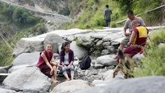 Tibetan buddhist monks rest at water creek waterfall with friends, India Stock Footage