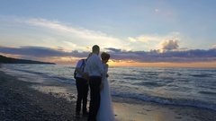 Wedding. Newly married couple on the beach at sunset talking with camera man. Arkistovideo