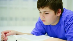 Teen boy reading a book. 13 years of age Stock Footage