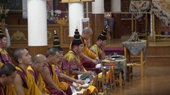 Tibetan monks chant mantras, ceremony, prayers, colorful costumes, hats Stock Footage