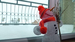 Toy handmade snowman against snowstorm behind the glass door. 4K shot Stock Footage