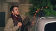 Man takes Christmas tree off the car and into the house through the garage Stock Footage