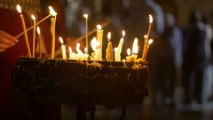 Close up of prayers hands lighting candles in the Holy Sepulchre Church in Stock Footage