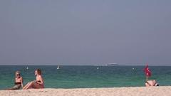 Women on the beach enjoying holiday cruise ship sailing on ocean Dubai winter 4K Stock Footage