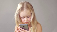 Little European girl playing with a smartphone. Close-up, even light Stock Footage