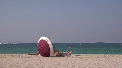 Dubai beach 4K girls under sun umbrella sunbath on ocean coast lifeguard oversee Stock Footage