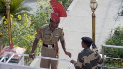 2 Indian soldiers talk, drops phone, Wagah border crossing, colorful uniform Stock Footage