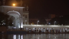 Sikh devotee worship around Golden Temple lake, night time, Amritsar, India Stock Footage