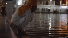 Old bearded Sikh man bathes and drinks, Golden Temple lake, Amritsar, India Stock Footage